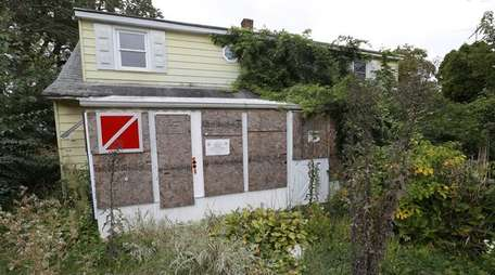 Abandoned homes, like this one in Levittown, seen