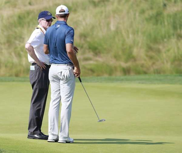 Dustin Johnson of the US talks with a