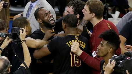 Cleveland Cavaliers forward LeBron James, top left, celebrates