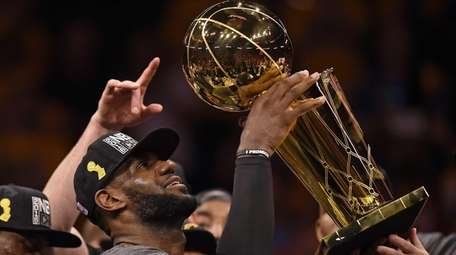 Cleveland Cavaliers' LeBron James (23) holds up the