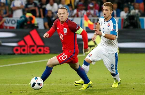 England's Wayne Rooney, left, runs with the ball