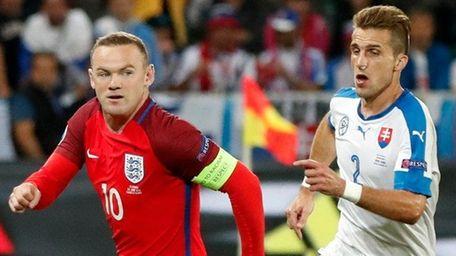 England's Wayne Rooney, left, runs with the ball
