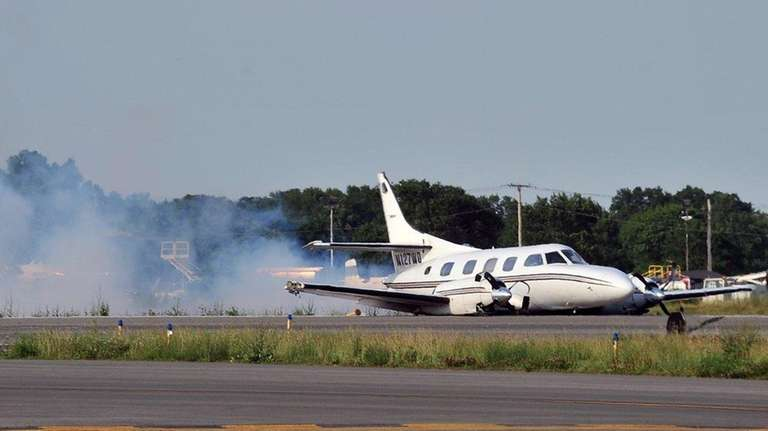 A twin-engine airplane smokes seconds after making a