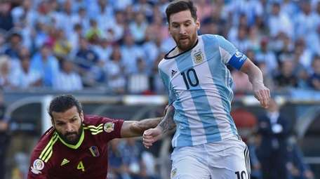 Argentina's Lionel Messi vies for the ball with