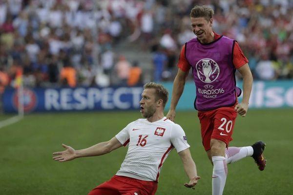 Poland's Jakub Blaszczykowski, bottom, celebrates scoring his side's
