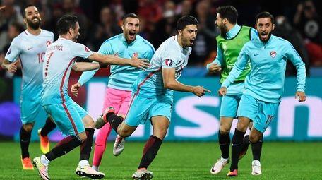 Ozan Tufan of Turkey (C) celebrates scoring his
