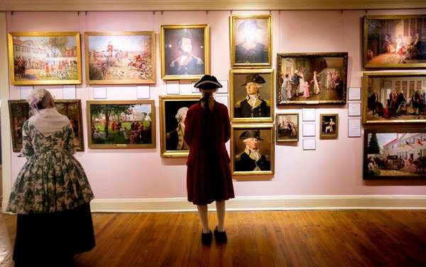 People look at an exhibition of John Ward