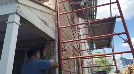 Workers strip paint and treat wood with linseed