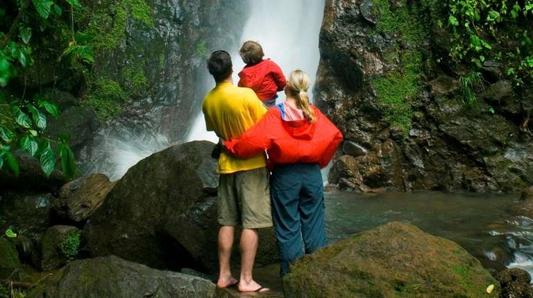 A family enjoys a waterfall at Arenal Hanging