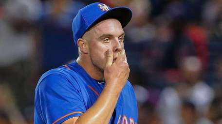 Mets relief pitcher Addison Reed walks off the