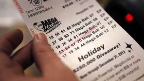A cashier holds a Mega Millions lottery ticket