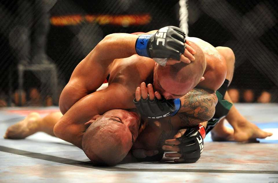 Georges St-Pierre, top, battles Thiago Alves during their