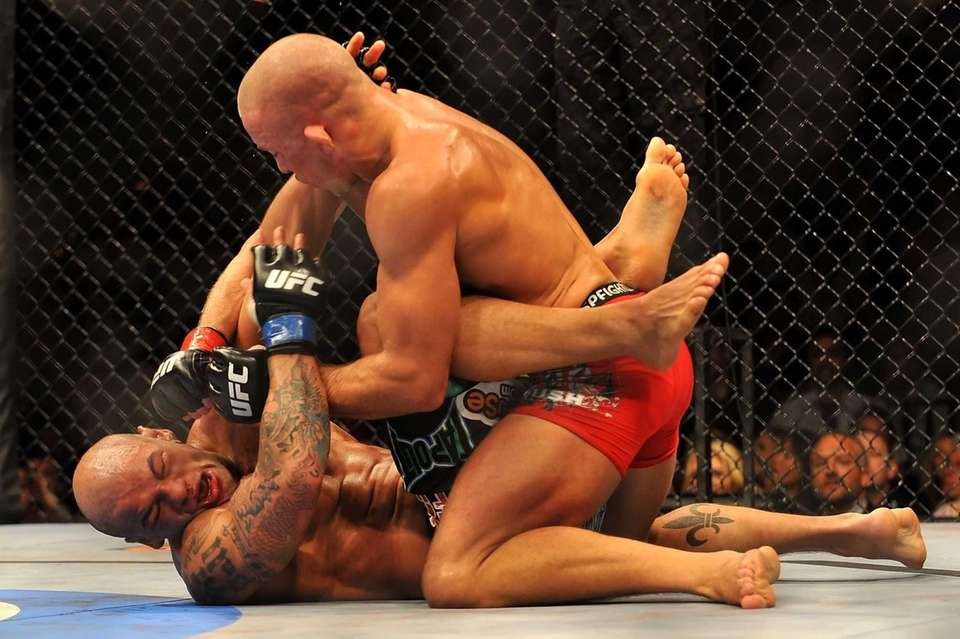 Georges St. Pierre, top, battles Thiago Alves during