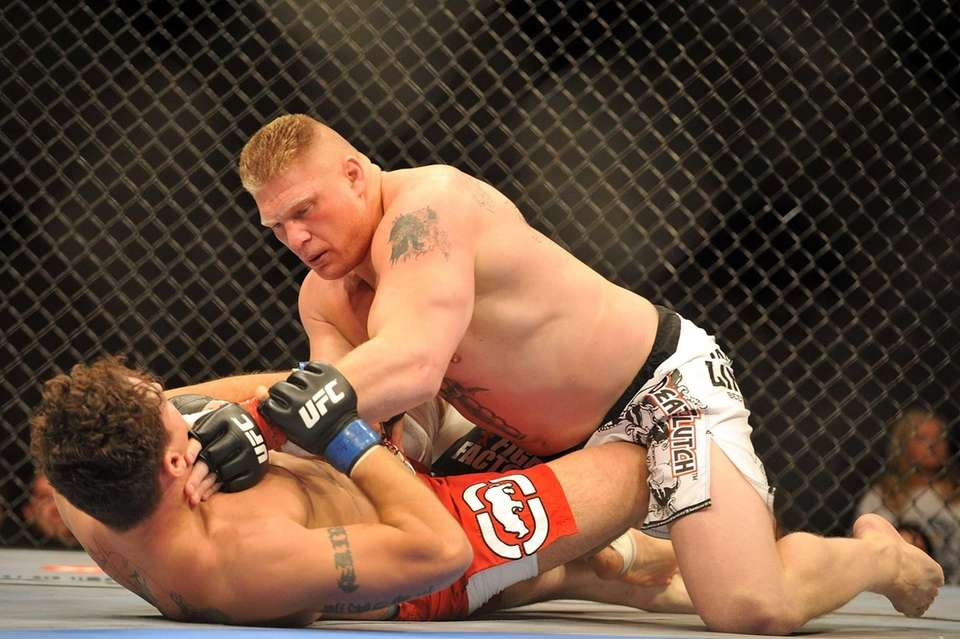 Brock Lesnar holds down Frank Mir during their