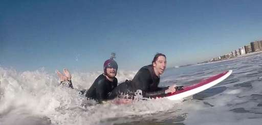 Dylan Hronec, right, surfs with his friend Mike