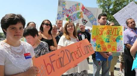 Advocates hold signs as they rallied in Mineola