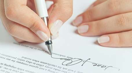 Woman signing a business contract.