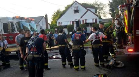 Firefighters work at a house fire on Park