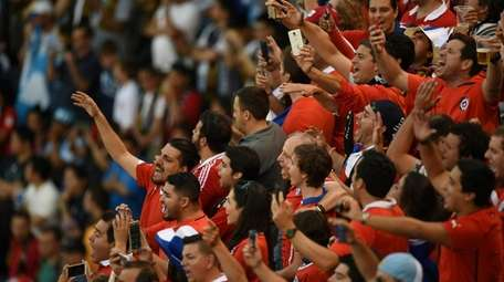 Supporters of Chile cheer for their team the