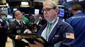 Trader Richard Cohen, right, works on the floor