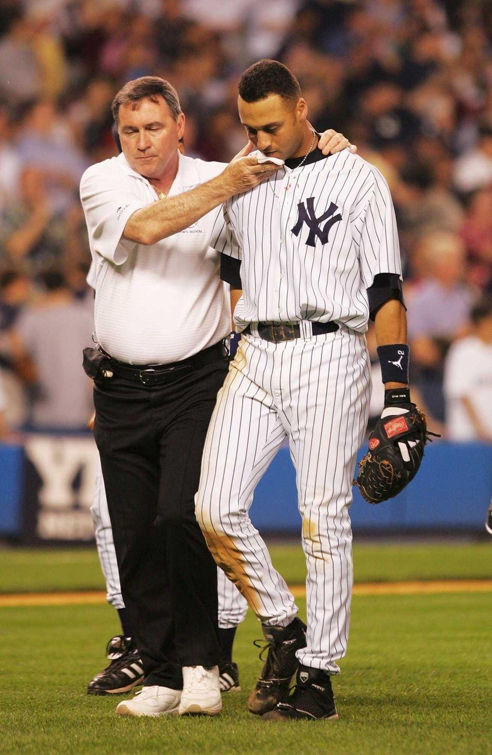 Trainer Gene Monahan helps Derek Jeter of the