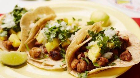 Tacos al pastor are served on corn tortillas