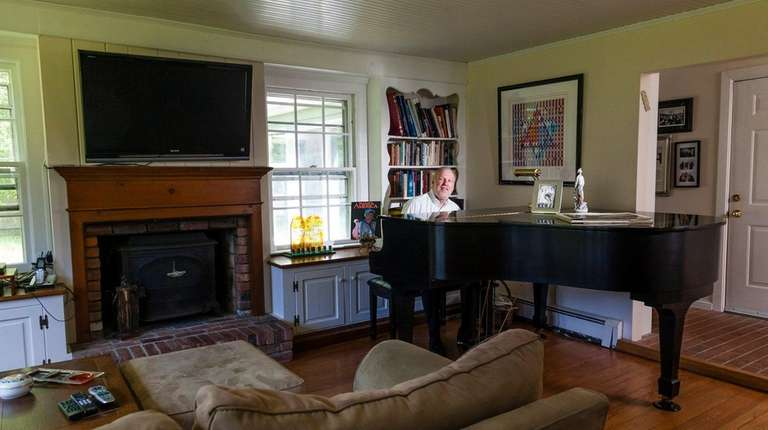 Larry Raful sits at his piano on June