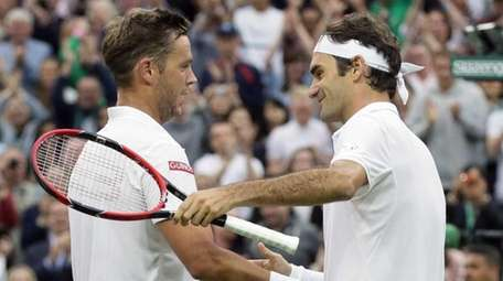 Roger Federer of Switzerland, right, shakes hands with