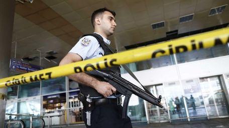 An armed Turkish policeman patrols behind a police