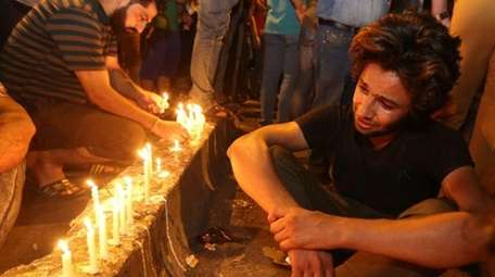 People light candles at the scene of a