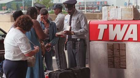A skycap inspects airline tickets for TWA passengers