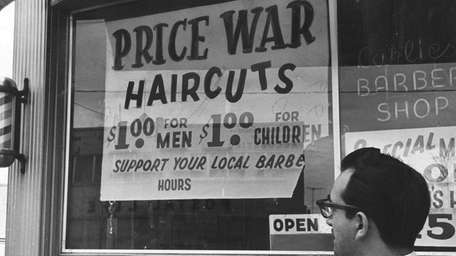A pedestrian ponders the dollar haircuts featured on