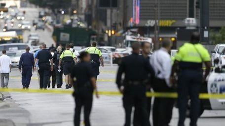 Investigators walk the scene of a shooting in