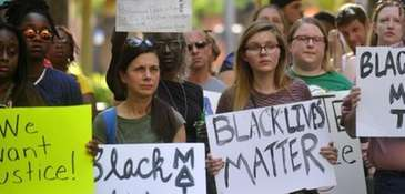 Protesters hold signs during a Black Lives Matter