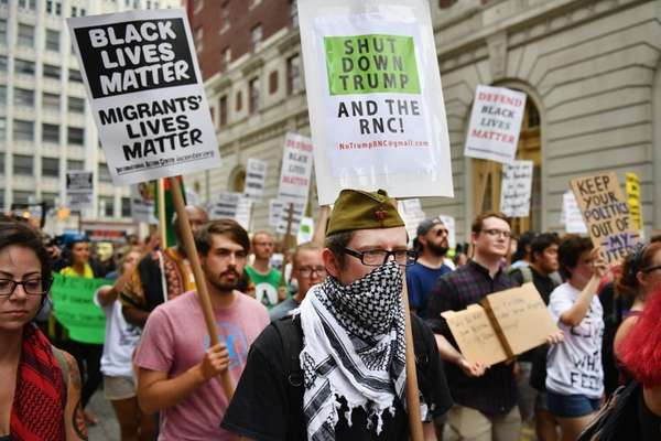 Demonstrators march through downtown ahead of the Republican