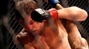 Darren Elkins, top, fights Godofredo Pepey, of Brazil,