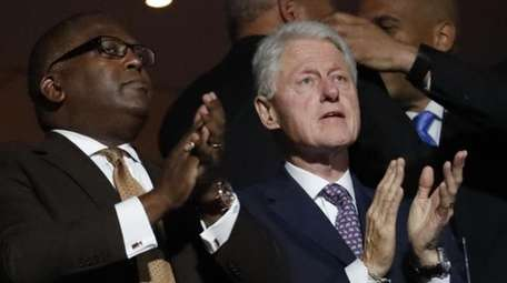 Former President Bill Clinton applauds as first lady
