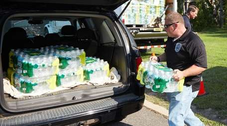Scott Proser helps load water bottles that will