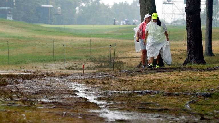 Women walk by the 18th hole after third