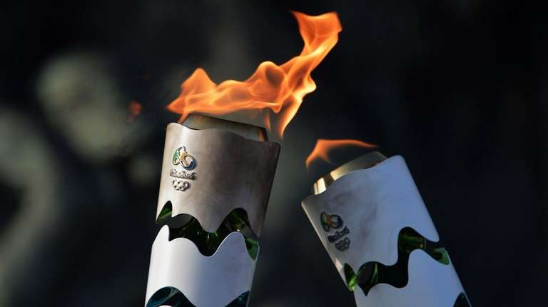 Brazilian residents pass the Olympic torch at Independence