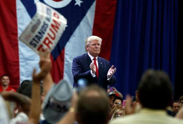 Donald Trump applauds after speaking during a town-hall