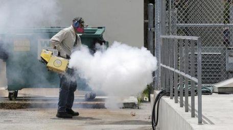 A Miami-Dade County mosquito control worker sprays around