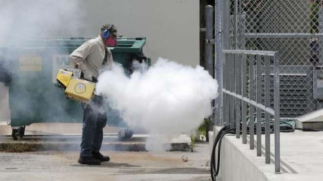A Miami-Dade County mosquito control worker sprays around