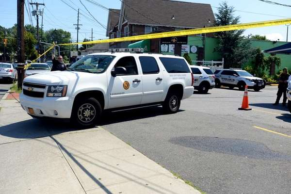 A medical examiner's vehicle leaves the scene where
