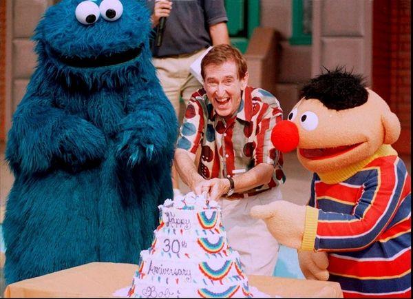 Bob McGrath cuts a 30th anniversary cake with