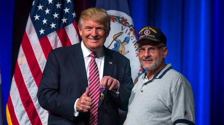Donald Trump holds a replica of a Purple