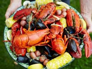 A plate of lobsters, mussels, clams, corn and