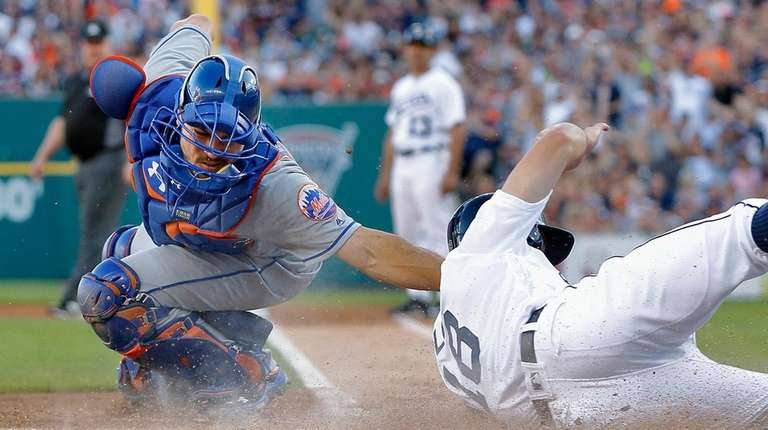 Detroit's Tyler Collins, right, beats the tag from