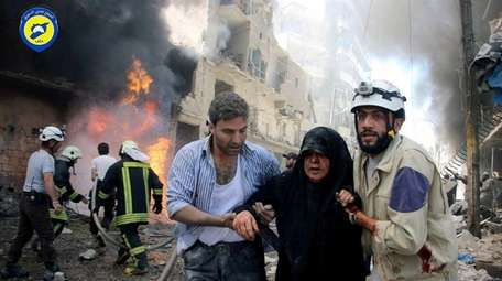 Syrian civil defense workers, right, help an injured