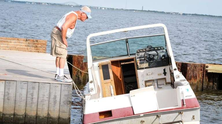 A man inspects a boat that was abandoned
